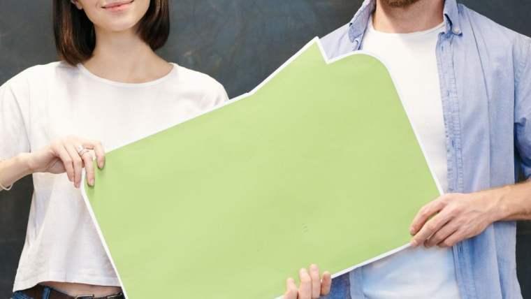 woman and man holding a green board